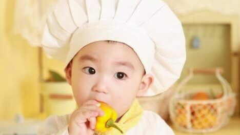 Image showing a child in a chef's hat eating a capsicum.